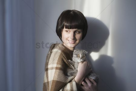 Animal head : Woman in blanket stands holding kitten