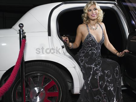 Curly hair : Woman in evening wear getting out of limousine
