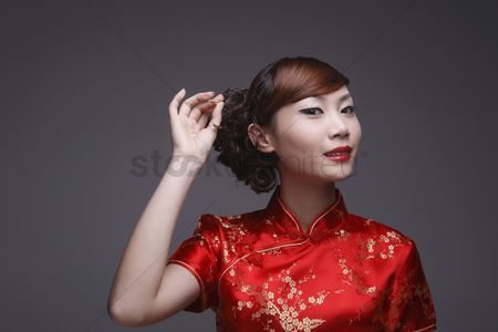Traditional clothing : Woman in red cheongsam pulling out hair pin from her hair