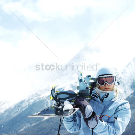 Outdoor : Woman in ski goggles holding snowboard