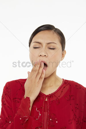 Traditional clothing : Woman in traditional clothing covering mouth while yawning