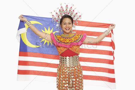 Bidayuh ethnicity : Woman in traditional clothing holding up a malaysian flag