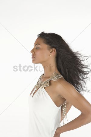 Elegance : Woman in white dress stands with eyes closed