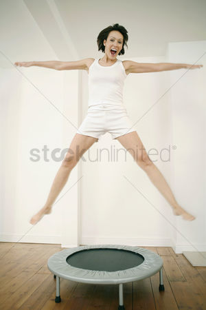 Enjoying : Woman jumping on a trampoline