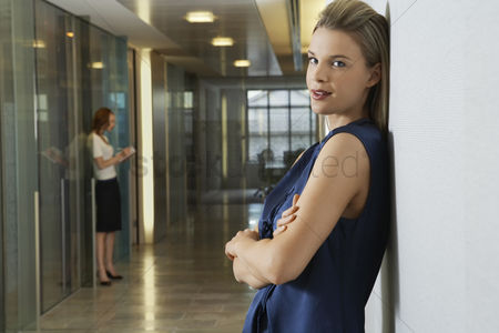 Interior background : Woman leaning against wall in office corridor portrait