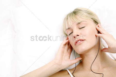 Satisfying : Woman listening to music on the bed