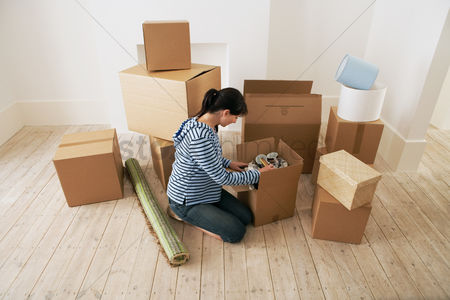 First : Woman looking at contents of moving boxes