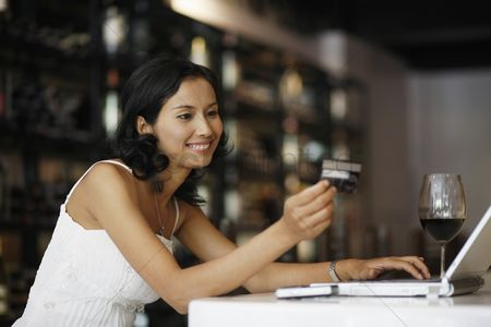Shopping : Woman looking at credit card while using laptop