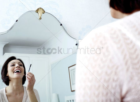 Attraction : Woman looking at the mirror  applying make-up