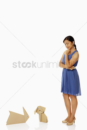 Bidayuh ethnicity : Woman looking at the paper dog and paper rabbit  contemplating