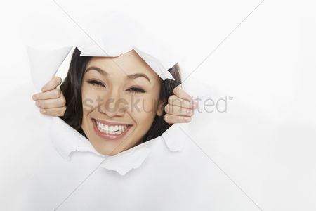 Smiling : Woman looking through a torn paper