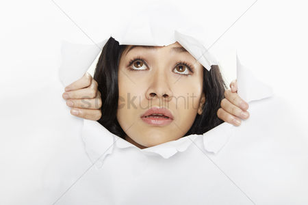 Malaysian : Woman looking through a torn paper