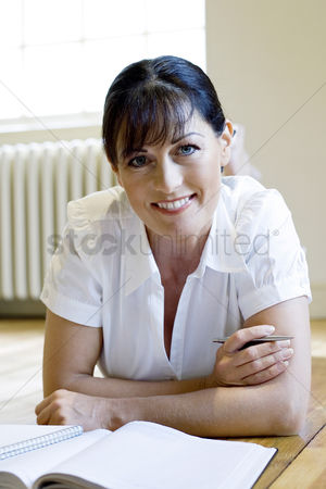 Lying forward : Woman lying forward on the floor smiling at the camera