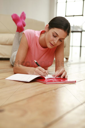 Lying forward : Woman lying forward on the floor writing diary