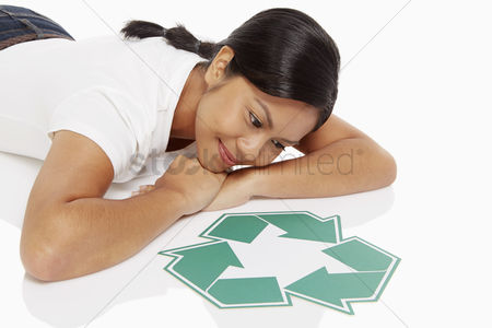 Bidayuh ethnicity : Woman lying on front  looking at a recycle logo