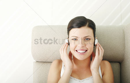 Lively : Woman lying on the couch listening to music on the headphones