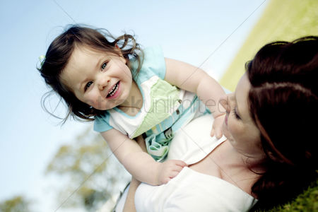 Enjoying : Woman lying on the grass holding her daughter