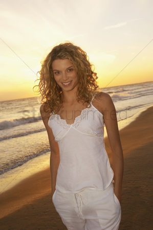 Curly hair : Woman on beach at sunset portrait