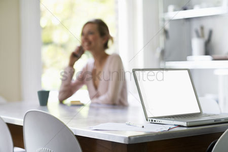 One person : Woman on phone sitting at kitchen table by laptop focus on laptop
