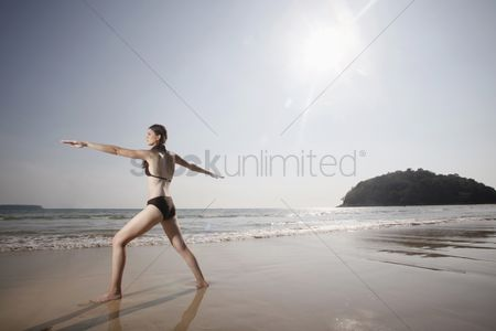 Practising yoga : Woman practising yoga on beach