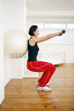 Strong : Woman pressing fitness ball against the wall while lifting dumbbells