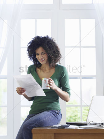 Sitting on lap : Woman reading document at home