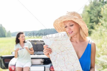 On the road : Woman reading map while friend leaning on convertible in background