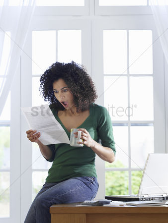 Sitting on lap : Woman reading paper document sitting on desk