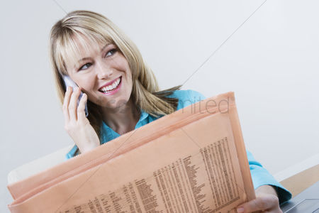 Cellular phone : Woman reading stock listings in newspaper