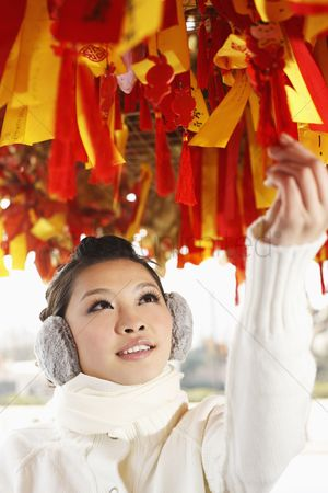 Traditional clothing : Woman reading wishes on the hanging ribbons