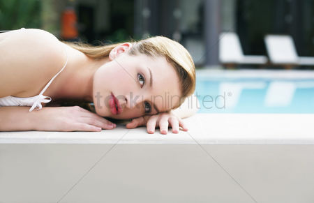 Lying forward : Woman relaxing by the pool side