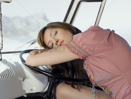 On the road : Woman resting on steering wheel in van half length