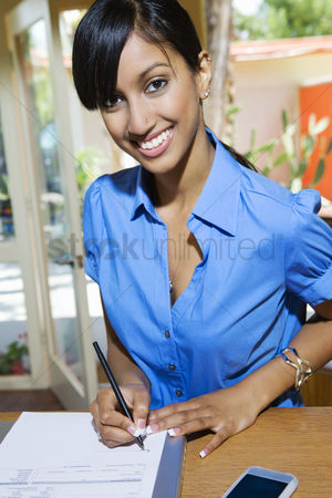 Posed : Woman signing paper