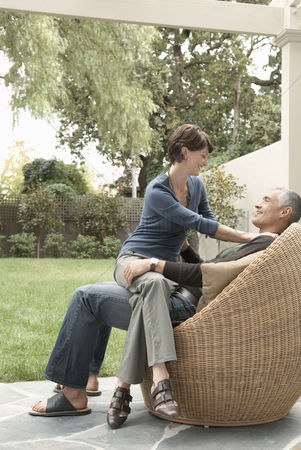 40 44 years : Woman sitting on husband s laps on patio
