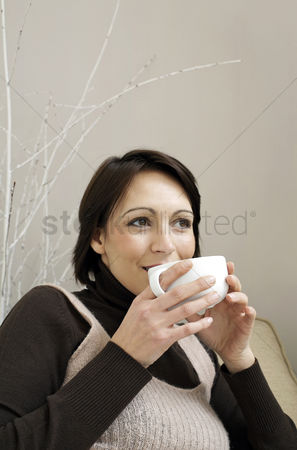 Housewife : Woman sitting on the couch holding a cup of coffee