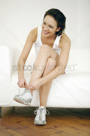 Lively : Woman sitting on the couch tying her shoelace