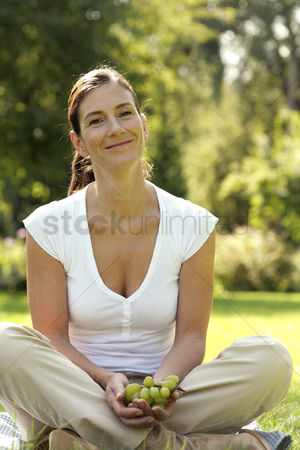 Smiling : Woman sitting on the field holding green grapes