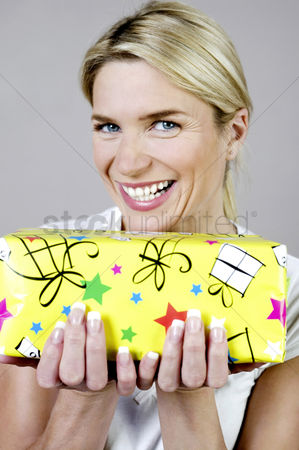 Birthday present : Woman smiling while holding a present