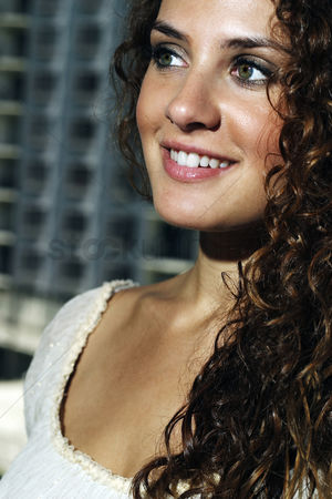 Cheerful : Woman smiling while looking away