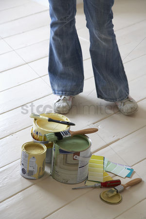 Paint brush : Woman standing by painting materials on floor