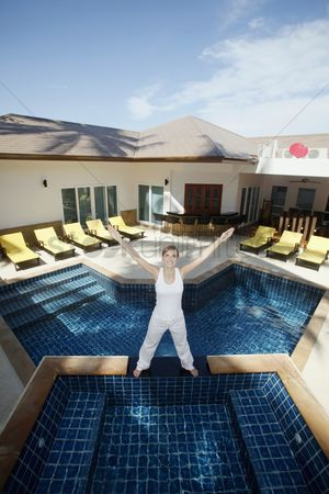 Practising yoga : Woman standing by the pool side with her hands up