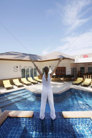 Practising yoga : Woman standing by the poolside with her hands raised
