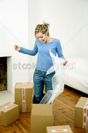 Denim : Woman standing in a box holding bubble pack