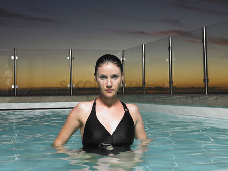 Swimmer : Woman standing in outdoor swimming pool at sunset