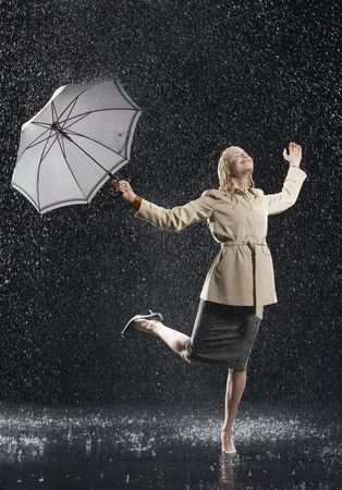 Celebrating : Woman standing on one leg holding umbrella leaning into falling rain