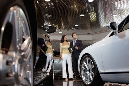 Show : Woman standing with auto salesman in car showroom
