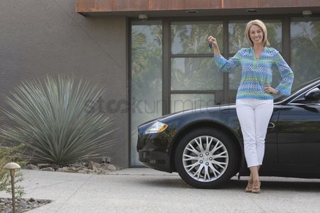 Transportation : Woman stands holding keys to luxury vehicle