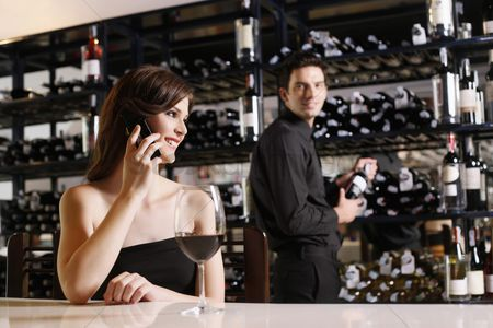 Wine bottle : Woman talking on the phone  man selecting wine bottle in the background