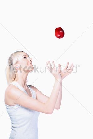 British ethnicity : Woman tossing apple in the air