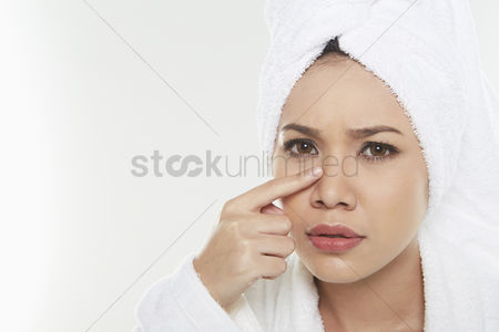 Frowning : Woman touching her face